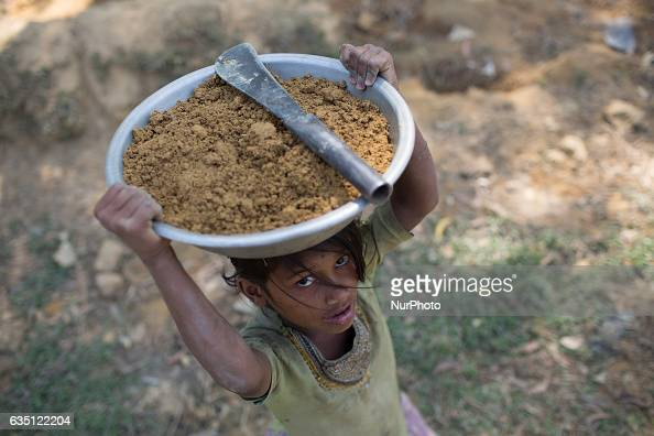 A Rohingya refugee girl carries mud in a bowl in Kutupalong Refugee Camp Cox's Bazar Bangladesh on February 13 2017 After attacks by Rohingya...
