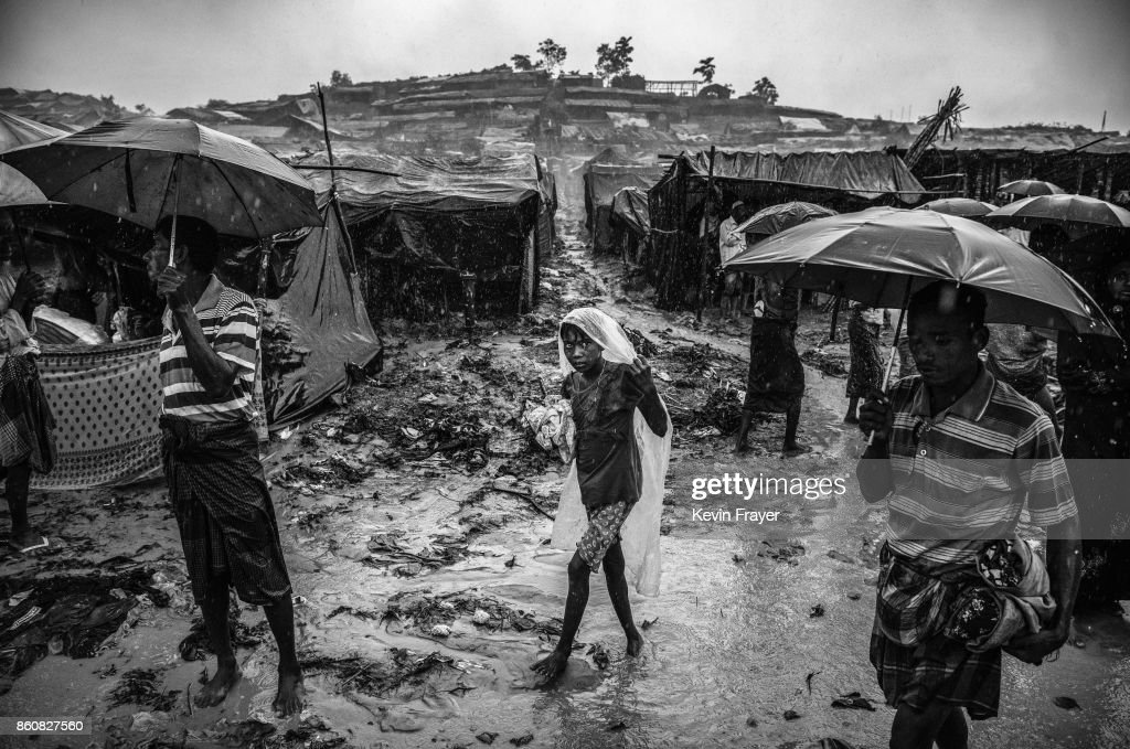 COX'S BAZAR, BANGLADESH - SEPTEMBER 19: A Rohingya refugee girl wears a plastic bag as she walks in the monsoon rains at the Palongkali refugee camp on September 19, 2017 in Cox's Bazar, Bangladesh. More than half a million Rohingya refugees have flooded into Bangladesh to flee an offensive by Myanmar's military that the United Nations has called 'a textbook example of ethnic cleansing'. The refugee population is expected to swell further, with thousands more Rohingya Muslims said to be making the perilous journey on foot toward the border, or paying smugglers to take them across by water in wooden boats. Hundreds are known to have died trying to escape, and survivors arrive with horrifying accounts of villages burned, women raped, and scores killed in the 'clearance operations' by Myanmar's army and Buddhist mobs that were sparked by militant attacks on security posts in Rakhine state on August 25, 2017. What the Rohingya refugees flee to is a different kind of suffering in sprawling makeshift camps rife with fears of malnutrition, cholera, and other diseases. Aid organizations are struggling to keep pace with the scale of need and the staggering number of them - an estimated 60 percent - who are children arriving alone. Bangladesh, whose acceptance of the refugees has been praised by humanitarian officials for saving lives, has urged the creation of an internationally-recognized 'safe zone' where refugees can return, though Rohingya Muslims have long been persecuted in predominantly Buddhist Myanmar. World leaders are still debating how to confront the country and its de facto leader, Aung San Suu Kyi, a Nobel Peace Prize laureate who championed democracy, but now appears unable or unwilling to stop the army's brutal crackdown.