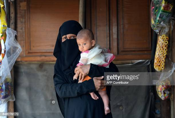A Rohingya refugee holds her child at a shop near their shelter in New Delhi on September 17 2017 Detested in Myanmar the Muslim Rohingya desperately...