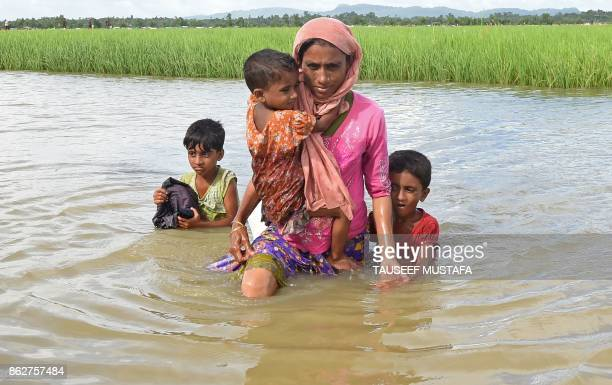 TOPSHOT Rohingya refugee Khalida a mother of three children wade across a canal near the no man's land area between Bangladesh and Myanmar in the...