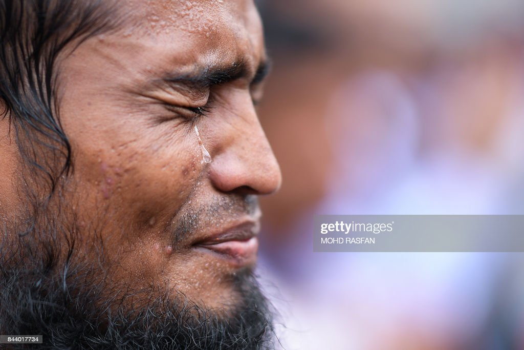 Rohingya refugee living in Malaysia cries as he offers prayers during a protest against the treatment of Rohingya Muslims in Myanmar, in Kuala Lumpur on September 8, 2017. Hundreds of protestors chanting 'Long live Rohingya' demonstrated outside the Myanmar embassy in the Malaysian capital on September 8 to condemn the deadly violence against the Muslim minority. / AFP PHOTO / Mohd RASFAN