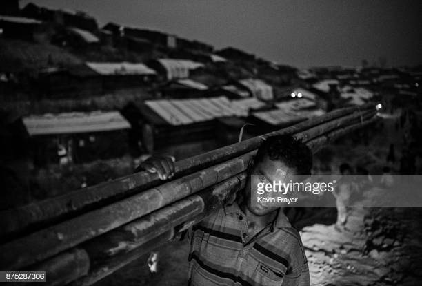 COX'S BAZAR BANGLADESH OCTOBER 29 A Rohingya refugee man carries bamboo to be used to build a shelter on October 27 2017 at the Balukhali refugee...