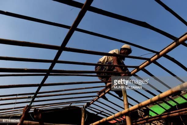 Rohingya refugee rebuilds his makeshift shelter at Balukhali refugee camp in the Bangladeshi district of Ukhia on November 22 2017 An estimated...