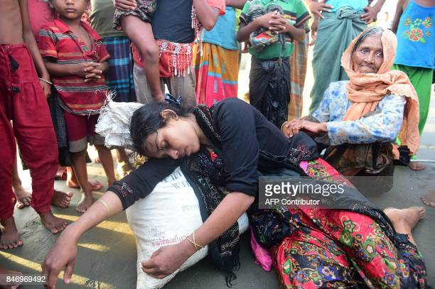 A Rohingya refugee rests after crossing the border from Myanmar by boat on the Bangladeshi shore of the Naf river in Teknaf on September 14 2017...