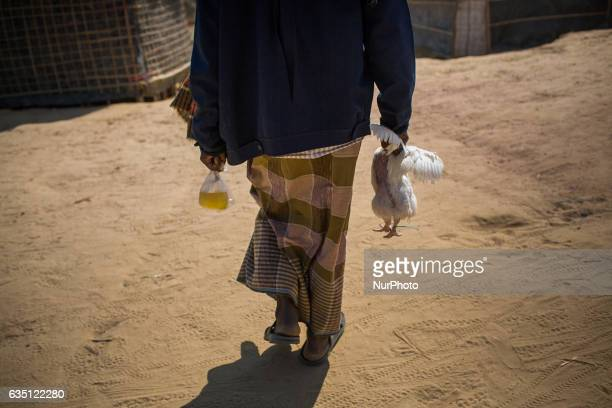 A Rohingya refugee returns home after buying oil and chicken for dinner at Kutupalong Refugee Camp Cox's Bazar Bangladesh on February 13 2017 After...
