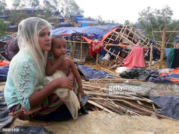A Rohingya refugee sits near a house destroyed by Cyclone Mora in a camp in the Cox's Bazar district on May 31 2017 Aid workers warned May 31 of an...