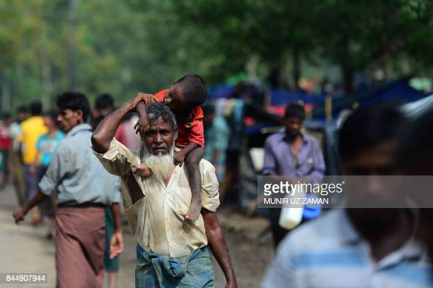 A Rohingya refugee walks while carrying his grand child at Kutupalong refugee camp in Bangladeshi district of Ukhia on September 9 2017 Nearly 300000...