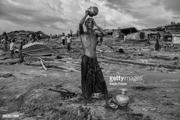 COX'S BAZAR BANGLADESH SEPTEMBER 26 A Rohingya refugee washes at a well at the Palongkali refugee camp on September 26 2017 in Cox's Bazar Bangladesh...