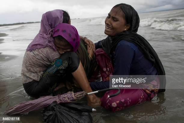Rohingya refugee woman break down in tears after jumping from a wooden boat that began to tip over as it hit the shore on September 12 2017 in...