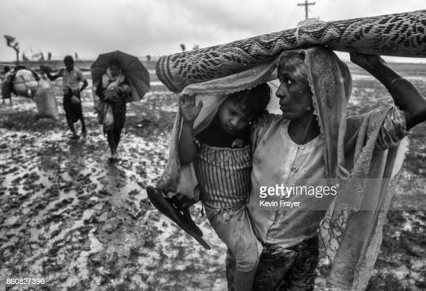 COX'S BAZAR BANGLADESH SEPTEMBER 28 A Rohingya refugee woman carries a child after arriving on the Bangladesh side of the Naf River at Shah Porir...