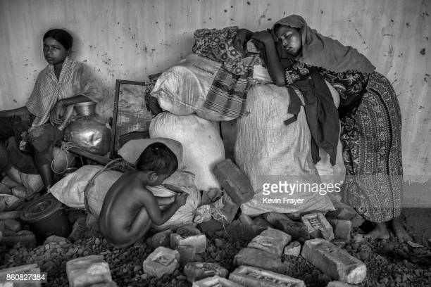 COX'S BAZAR BANGLADESH SEPTEMBER 25 A Rohingya refugee woman collapses on her bags from exhaustion after arriving on the Bangladesh side of the Naf...