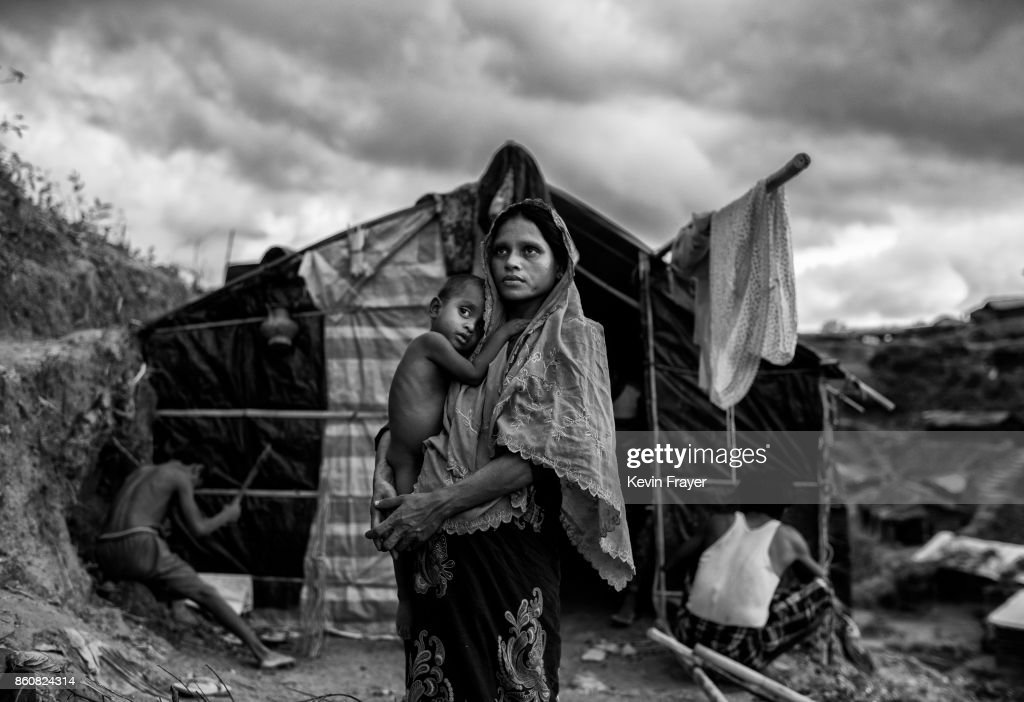 COX'S BAZAR, BANGLADESH - SEPTEMBER 27: A Rohingya refugee woman holds her child as she stands outside her shelter at the sprawling Balukali refugee camp on September 27, 2017 in Cox's Bazar, Bangladesh. More than half a million Rohingya refugees have flooded into Bangladesh to flee an offensive by Myanmar's military that the United Nations has called 'a textbook example of ethnic cleansing'. The refugee population is expected to swell further, with thousands more Rohingya Muslims said to be making the perilous journey on foot toward the border, or paying smugglers to take them across by water in wooden boats. Hundreds are known to have died trying to escape, and survivors arrive with horrifying accounts of villages burned, women raped, and scores killed in the 'clearance operations' by Myanmar's army and Buddhist mobs that were sparked by militant attacks on security posts in Rakhine state on August 25, 2017. What the Rohingya refugees flee to is a different kind of suffering in sprawling makeshift camps rife with fears of malnutrition, cholera, and other diseases. Aid organizations are struggling to keep pace with the scale of need and the staggering number of them - an estimated 60 percent - who are children arriving alone. Bangladesh, whose acceptance of the refugees has been praised by humanitarian officials for saving lives, has urged the creation of an internationally-recognized 'safe zone' where refugees can return, though Rohingya Muslims have long been persecuted in predominantly Buddhist Myanmar. World leaders are still debating how to confront the country and its de facto leader, Aung San Suu Kyi, a Nobel Peace Prize laureate who championed democracy, but now appears unable or unwilling to stop the army's brutal crackdown.