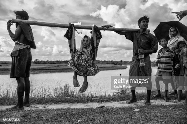 COX'S BAZAR BANGLADESH OCTOBER 02 A Rohingya refugee woman is carried by relatives near the border on the Bangladesh side of the Naf River after...