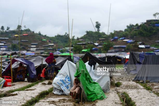 Rohingya refugee woman sits next to a newly built makeshift shelter in a camp in the Bangladeshi locality of Ukhia on September 9 2017 Nearly 300000...