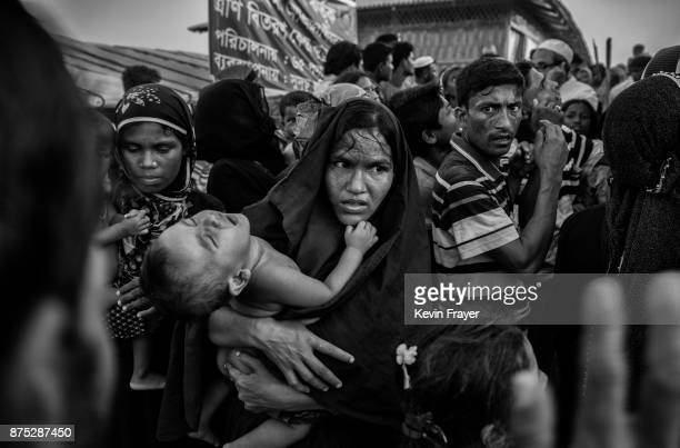 COX'S BAZAR BANGLADESH OCTOBER 27 A Rohingya refugee woman struggles in the crowd to Gert food aid on October 27 2017 at the Kutupalong refugee camp...