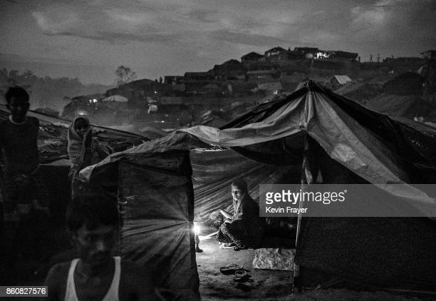 COX'S BAZAR BANGLADESH OCTOBER 01 A Rohingya refugee woman uses a candle to light her tent at the Palongkali refugee camp on October 1 2017 in Cox's...