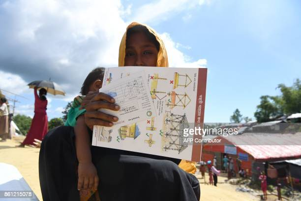 Rohingya refugee woman waits for her husband after collecting health and sanitation aid at the the Balukhali refugee camp in the Bangladeshi district...