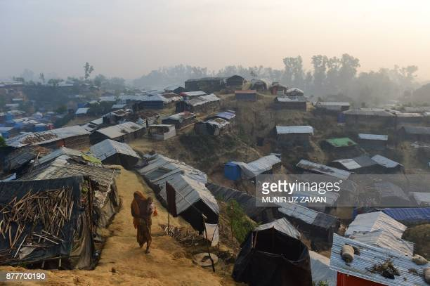 Rohingya refugee woman walks with a child in her lap in Balukhali refugee camp in the Bangladeshi district of Ukhia on November 23 2017 An estimated...