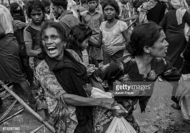 COX'S BAZAR BANGLADESH OCTOBER 30 Rohingya refugee women fight over a bag of rice as a WFP aid depot is ransacked following an event held by...