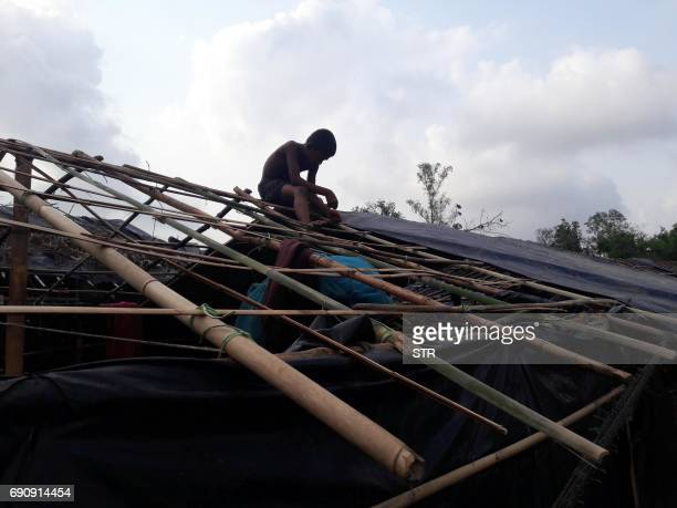 Rohingya refugee works on his house which was destroyed by Cyclone Mora at a camp in the Cox's Bazar district on May 31 2017 Aid workers warned May...