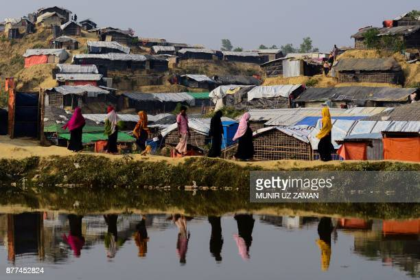 TOPSHOT Rohingya refugees are reflected on a pond as they walk back to their homes at Balukhali refugee camp in the Bangladeshi district of Ukhia on...