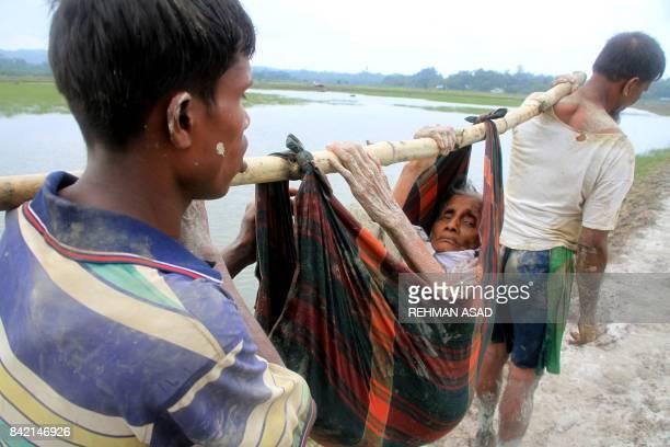 TOPSHOT Rohingya refugees carry an elderly woman from Rakhine state in Myanmar along a path near Teknaf in Bangladesh on September 3 2017 Around 400...