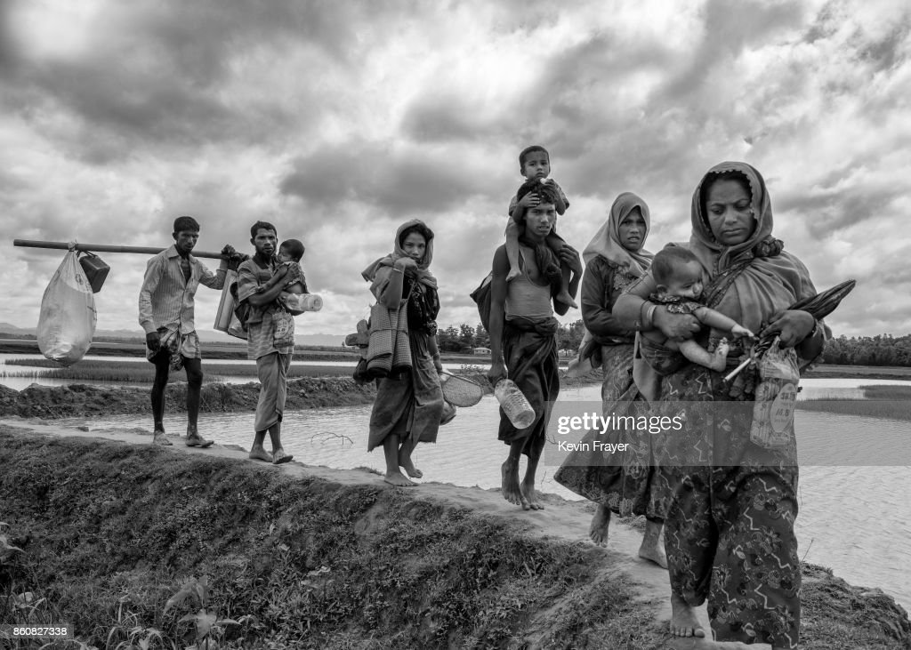 COX'S BAZAR, BANGLADESH - SEPTEMBER 24: Rohingya refugees carry their belongings as they walk after crossing the border on the Bangladesh side of the Naf River while fleeing Myanmar, on September 24, 2017 in Cox's Bazar, Bangladesh. More than half a million Rohingya refugees have flooded into Bangladesh to flee an offensive by Myanmar's military that the United Nations has called 'a textbook example of ethnic cleansing'. The refugee population is expected to swell further, with thousands more Rohingya Muslims said to be making the perilous journey on foot toward the border, or paying smugglers to take them across by water in wooden boats. Hundreds are known to have died trying to escape, and survivors arrive with horrifying accounts of villages burned, women raped, and scores killed in the 'clearance operations' by Myanmar's army and Buddhist mobs that were sparked by militant attacks on security posts in Rakhine state on August 25, 2017. What the Rohingya refugees flee to is a different kind of suffering in sprawling makeshift camps rife with fears of malnutrition, cholera, and other diseases. Aid organizations are struggling to keep pace with the scale of need and the staggering number of them - an estimated 60 percent - who are children arriving alone. Bangladesh, whose acceptance of the refugees has been praised by humanitarian officials for saving lives, has urged the creation of an internationally-recognized 'safe zone' where refugees can return, though Rohingya Muslims have long been persecuted in predominantly Buddhist Myanmar. World leaders are still debating how to confront the country and its de facto leader, Aung San Suu Kyi, a Nobel Peace Prize laureate who championed democracy, but now appears unable or unwilling to stop the army's brutal crackdown.