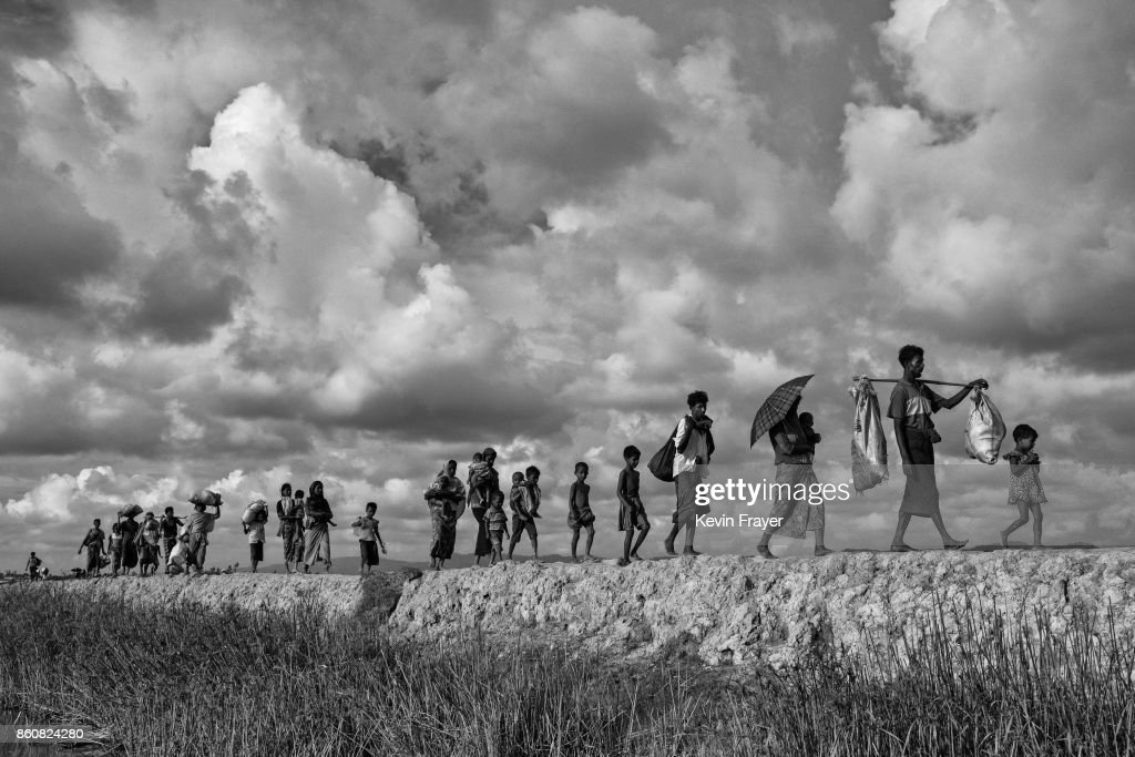 COX'S BAZAR, BANGLADESH - OCTOBER 02: Rohingya refugees carry their belongings as they walk on the Bangladesh side of the Naf River after fleeing Myanmar, on October 2, 2017 in Cox's Bazar, Bangladesh. More than half a million Rohingya refugees have flooded into Bangladesh to flee an offensive by Myanmar's military that the United Nations has called 'a textbook example of ethnic cleansing'. The refugee population is expected to swell further, with thousands more Rohingya Muslims said to be making the perilous journey on foot toward the border, or paying smugglers to take them across by water in wooden boats. Hundreds are known to have died trying to escape, and survivors arrive with horrifying accounts of villages burned, women raped, and scores killed in the 'clearance operations' by Myanmar's army and Buddhist mobs that were sparked by militant attacks on security posts in Rakhine state on August 25, 2017. What the Rohingya refugees flee to is a different kind of suffering in sprawling makeshift camps rife with fears of malnutrition, cholera, and other diseases. Aid organizations are struggling to keep pace with the scale of need and the staggering number of them - an estimated 60 percent - who are children arriving alone. Bangladesh, whose acceptance of the refugees has been praised by humanitarian officials for saving lives, has urged the creation of an internationally-recognized 'safe zone' where refugees can return, though Rohingya Muslims have long been persecuted in predominantly Buddhist Myanmar. World leaders are still debating how to confront the country and its de facto leader, Aung San Suu Kyi, a Nobel Peace Prize laureate who championed democracy, but now appears unable or unwilling to stop the army's brutal crackdown.
