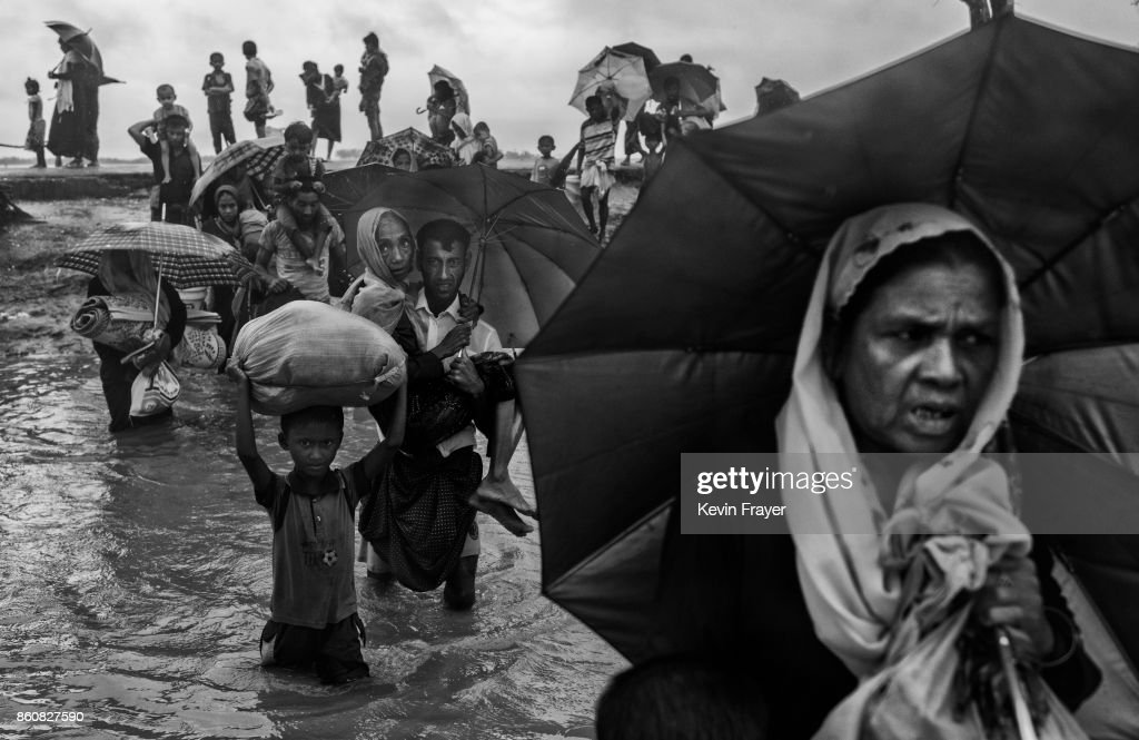 COX'S BAZAR, BANGLADESH - SEPTEMBER 28: Rohingya refugees carry their belongings as they walk through water on the Bangladesh side of the Naf River after fleeing their village in Myanmar, on September 28, 2017 in Cox's Bazar, Bangladesh. More than half a million Rohingya refugees have flooded into Bangladesh to flee an offensive by Myanmar's military that the United Nations has called 'a textbook example of ethnic cleansing'. The refugee population is expected to swell further, with thousands more Rohingya Muslims said to be making the perilous journey on foot toward the border, or paying smugglers to take them across by water in wooden boats. Hundreds are known to have died trying to escape, and survivors arrive with horrifying accounts of villages burned, women raped, and scores killed in the 'clearance operations' by Myanmar's army and Buddhist mobs that were sparked by militant attacks on security posts in Rakhine state on August 25, 2017. What the Rohingya refugees flee to is a different kind of suffering in sprawling makeshift camps rife with fears of malnutrition, cholera, and other diseases. Aid organizations are struggling to keep pace with the scale of need and the staggering number of them - an estimated 60 percent - who are children arriving alone. Bangladesh, whose acceptance of the refugees has been praised by humanitarian officials for saving lives, has urged the creation of an internationally-recognized 'safe zone' where refugees can return, though Rohingya Muslims have long been persecuted in predominantly Buddhist Myanmar. World leaders are still debating how to confront the country and its de facto leader, Aung San Suu Kyi, a Nobel Peace Prize laureate who championed democracy, but now appears unable or unwilling to stop the army's brutal crackdown.
