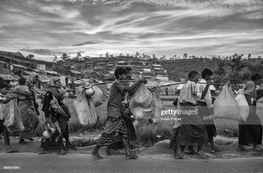 COX'S BAZAR, BANGLADESH -OCTOBER 02: Rohingya refugees carry their belongings on a road as they arrive after fleeing Myanmar to the Palongkali refugee camp on October 2, 2017 in Cox's Bazar, Bangladesh. More than half a million Rohingya refugees have flooded into Bangladesh to flee an offensive by Myanmar's military that the United Nations has called 'a textbook example of ethnic cleansing'. The refugee population is expected to swell further, with thousands more Rohingya Muslims said to be making the perilous journey on foot toward the border, or paying smugglers to take them across by water in wooden boats. Hundreds are known to have died trying to escape, and survivors arrive with horrifying accounts of villages burned, women raped, and scores killed in the 'clearance operations' by Myanmar's army and Buddhist mobs that were sparked by militant attacks on security posts in Rakhine state on August 25, 2017. What the Rohingya refugees flee to is a different kind of suffering in sprawling makeshift camps rife with fears of malnutrition, cholera, and other diseases. Aid organizations are struggling to keep pace with the scale of need and the staggering number of them - an estimated 60 percent - who are children arriving alone. Bangladesh, whose acceptance of the refugees has been praised by humanitarian officials for saving lives, has urged the creation of an internationally-recognized 'safe zone' where refugees can return, though Rohingya Muslims have long been persecuted in predominantly Buddhist Myanmar. World leaders are still debating how to confront the country and its de facto leader, Aung San Suu Kyi, a Nobel Peace Prize laureate who championed democracy, but now appears unable or unwilling to stop the army's brutal crackdown.