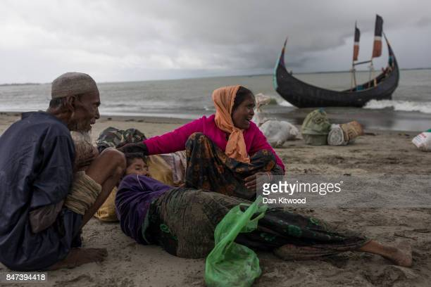 Rohingya refugees comfort an elderly woman after the wooden boat they were travelling on from Myanmar crashed into the shore and tipped everyone out...