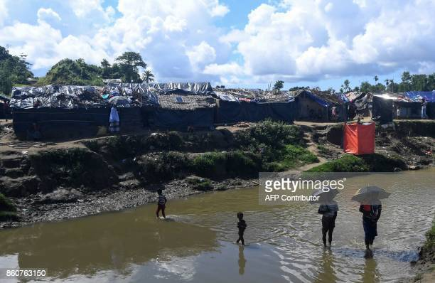 Rohingya refugees cross a narrow canal by their settlement in the no man's land between Myanmar and Bangladesh at Tumbru in Naikongchari district on...