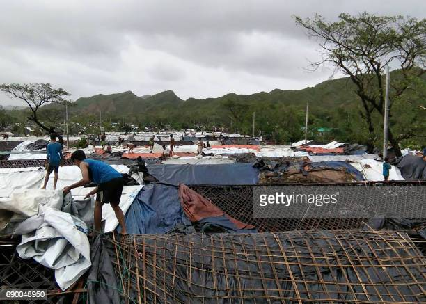 Rohingya refugees fix the damaged roofs of huts in a makeshift camp in Bangladesh's Cox's Bazar district on May 30 2017 after Cyclone Mora made...