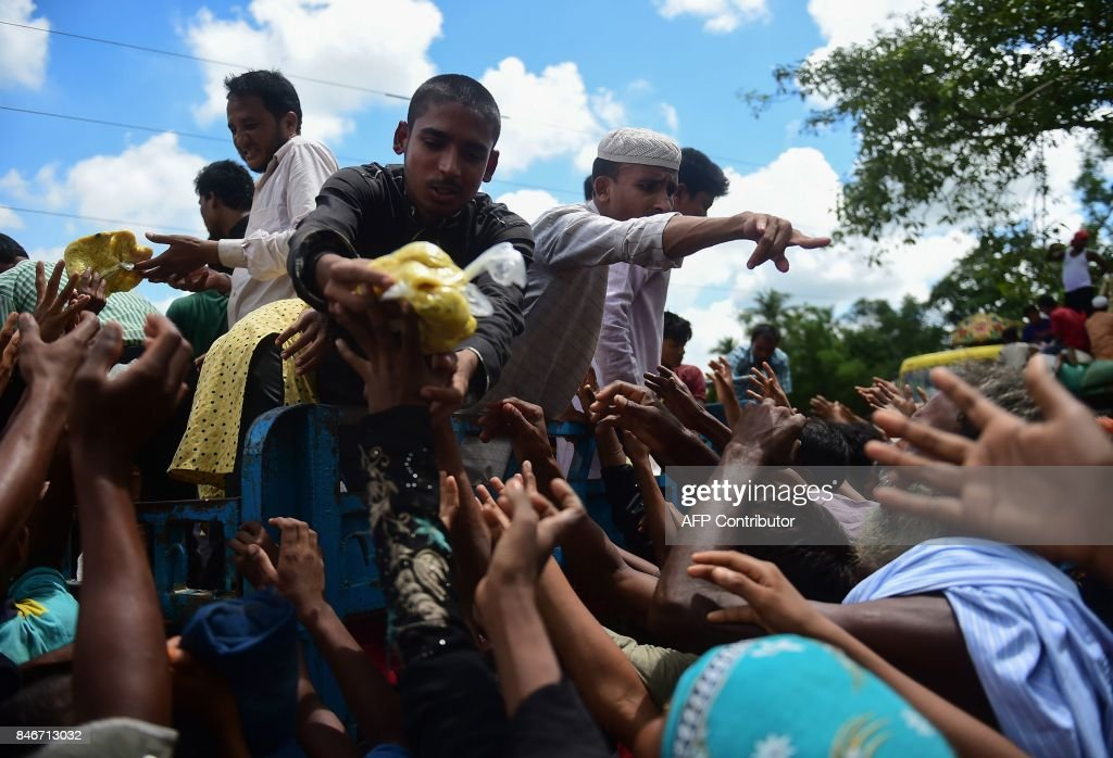 Rohingya refugees from Myanmar gather around a truck delivering food aid in Ukhia on September 14, 2017. Around 379,000 Rohingya have sought refuge in Bangladesh from violence in Myanmar's Rakhine state that started August 25, after Rohingya militants attacked police posts there. /