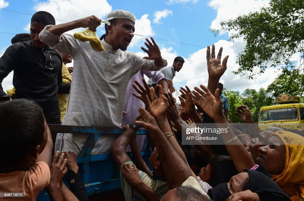 Rohingya refugees from Myanmar gesture towards a man on a truck delivering food aid in Ukhia on September 14, 2017. Around 379,000 Rohingya have sought refuge in Bangladesh from violence in Myanmar's Rakhine state that started August 25, after Rohingya militants attacked police posts there. /
