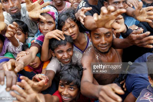 TOPSHOT Rohingya refugees from Myanmar's Rakhine state wait for aid at Kutupalong refugee camp in the Bangladeshi town of Teknaf on September 5 2017...