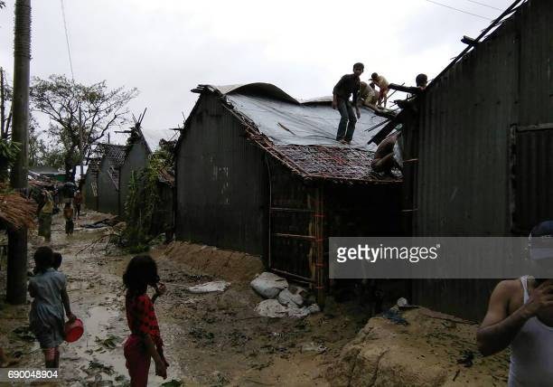 Rohingya refugees gather walk next to huts in a makeshift camp in Bangladesh's Cox's Bazar district on May 30 2017 after Cyclone Mora made landfall...