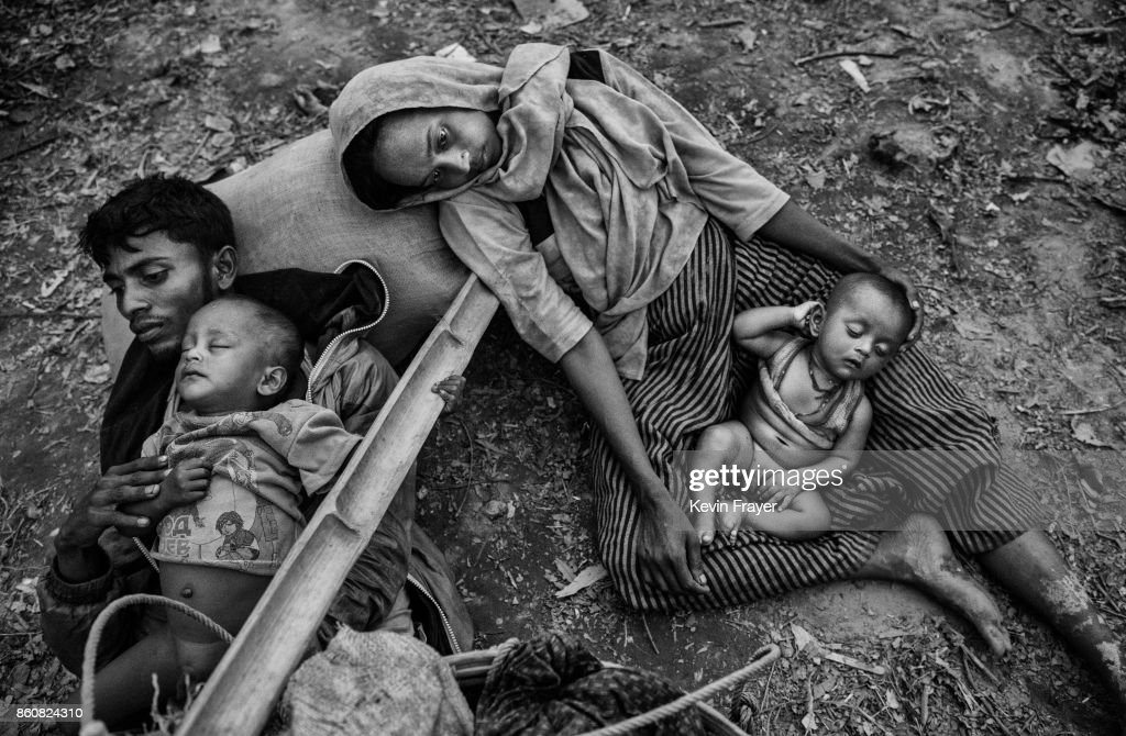 COX'S BAZAR, BANGLADESH - OCTOBER 02: A Rohingya refugee family rest as they sit on the ground on the Bangladesh side of the Naf River after fleeing Myanmar, on October 2, 2017 in Cox's Bazar, Bangladesh. More than half a million Rohingya refugees have flooded into Bangladesh to flee an offensive by Myanmar's military that the United Nations has called 'a textbook example of ethnic cleansing'. The refugee population is expected to swell further, with thousands more Rohingya Muslims said to be making the perilous journey on foot toward the border, or paying smugglers to take them across by water in wooden boats. Hundreds are known to have died trying to escape, and survivors arrive with horrifying accounts of villages burned, women raped, and scores killed in the 'clearance operations' by Myanmar's army and Buddhist mobs that were sparked by militant attacks on security posts in Rakhine state on August 25, 2017. What the Rohingya refugees flee to is a different kind of suffering in sprawling makeshift camps rife with fears of malnutrition, cholera, and other diseases. Aid organizations are struggling to keep pace with the scale of need and the staggering number of them - an estimated 60 percent - who are children arriving alone. Bangladesh, whose acceptance of the refugees has been praised by humanitarian officials for saving lives, has urged the creation of an internationally-recognized 'safe zone' where refugees can return, though Rohingya Muslims have long been persecuted in predominantly Buddhist Myanmar. World leaders are still debating how to confront the country and its de facto leader, Aung San Suu Kyi, a Nobel Peace Prize laureate who championed democracy, but now appears unable or unwilling to stop the army's brutal crackdown.