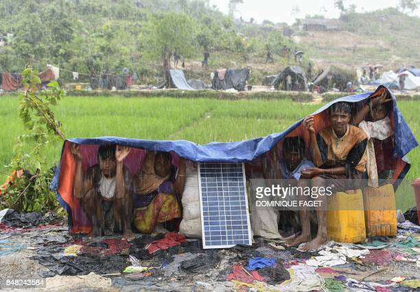 TOPSHOT Rohingya refugees protect themself from the rain in Bangladesh's Balukhali refugee camp on September 17 2017 Monsoon rain amid a drive to...