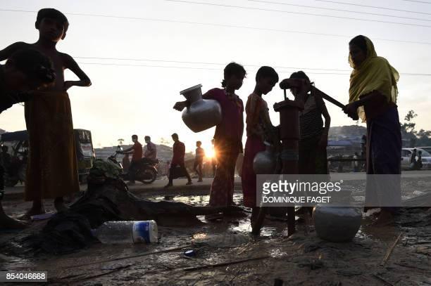 Rohingya refugees pump water at the refugee camp of Thwangkhaneari near the Bangladeshi locality of Ukhia on September 26 2017 Bangladesh has eased...