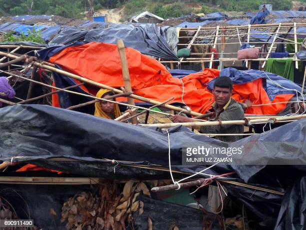 Rohingya refugees rebuild their house which was destroyed by Cyclone Mora at a camp in the Cox's Bazar district on May 31 2017 Aid workers warned May...