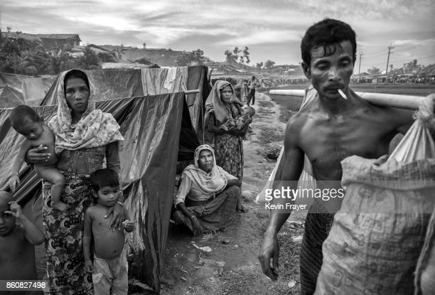 COX'S BAZAR BANGLADESH SEPTEMBER 24 Rohingya refugees sit in front of their makeshift shelters as other arrive carrying belongings at the Palongkali...