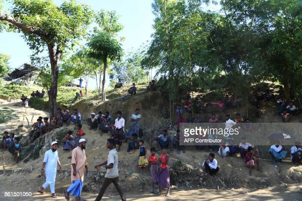 Rohingya refugees sit on a hill as they wait for aid trucks at the Balukhali refugee camp in the Bangladeshi district of Ukhia on October 15 2017...