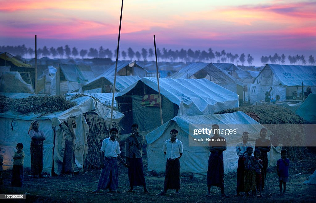Rohingya refugees stand at a crowded internally displaced persons (IDP) camp after sunset November 24, 2012 on the outskirts of Sittwe, Myanmar. An estimated 111,000 people were displaced by sectarian violence in June and October, effecting mostly the ethnic Rohingya people, who are now living in crowded IDP camps racially segregated from the Rakhine Buddhists in order to maintain stability. Around 89 lives were lost during a week of violence in October, the worst in decades. As of 2012, 800,000 Rohingya live in Myanmar. According to the UN, they are one of the most persecuted minorities in the world.