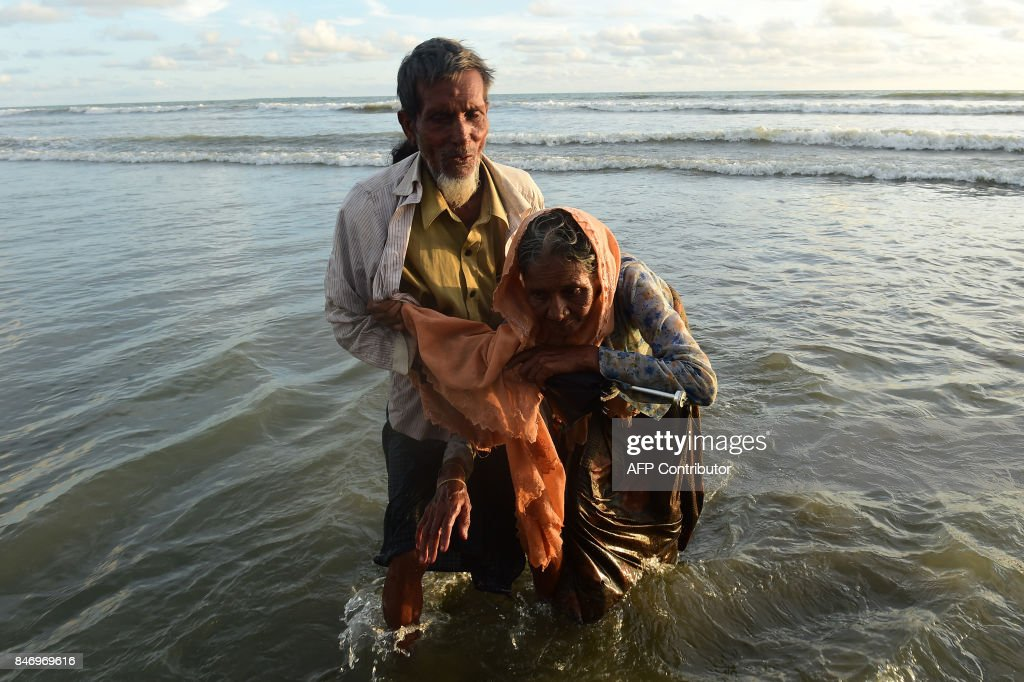 A Rohingya refugees wade after crossing the border from Myanmar by boat, on the Bangladeshi shore of the Naf river in Teknaf on September 14, 2017. Bangladeshi boat operators are exploiting Rohingya Muslims fleeing violence in Myanmar by demanding up to $100 for ferry trips that usually cost 50 cents, as the United Nations warned September 14 of a 'worst case scenario' in which the entire minority group tries to escape the unrest. Some 389,000 Rohingya - including 10,000 in the past 24 hours -- have fled across the border since late August and there have been growing appeals for Myanmar's leader Aung San Suu Kyi to speak out in their defence. ZAMAN
