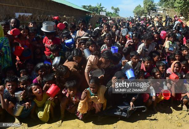 TOPSHOT Rohingya refugees wait for food aid at Thankhali refugee camp in Bangladesh's Ukhia district on November 14 2017 More than 600000 Rohingya...
