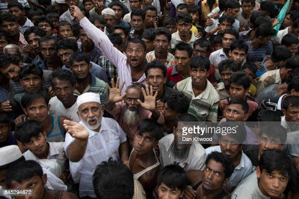 Rohingya refugees wait for sacks of rice to be distributed on September 10 2017 in Whaikhyang Bangladesh Recent reports have suggested that around...