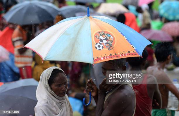 Rohingya refugees wait in the rain in an area near no man's land on the Bangladesh side of the border with Myanmar after crossing the Naf River after...