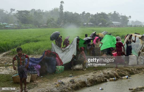Rohingya refugees wait under heavy rainfall in an area near no man's land on the Bangladesh side of the border with Myanmar after crossing the Naf...
