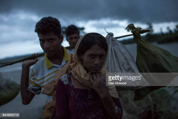 Rohingya refugees walk across Paddy fields in the pouring rain at dusk after crossing the border from Myanmar on September 09 2017 in Gundum...